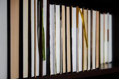 Lots of colourful thick open books stand on a dark background. Ready to read royalty free stock image