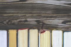 Lots of colourful thick open books stand on a dark background royalty free stock images