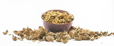 Lots of cracked open walnuts in a cup on a white background Stock Photos