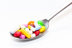 Pills on spoon. Lots of different pills on a spoon Royalty Free Stock Photography