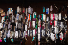 Lots of different shoes hanging in the showcase on market Royalty Free Stock Images