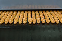 Lots of eclairs on conveyor. Royalty Free Stock Photo