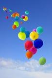 Lots farbige Ballone, die in den Himmel fliegen Stockbilder