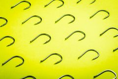 Lots of fishing hooks on yellow background. Fishing accessories and accessories stock image