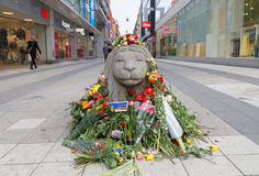 Lots of flowers on concrete lion in central Stockholm from peopl Stock Images