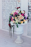 Lots of flowers in a white pot on a stalk. Many different flowers collected in one bouquet stand in a bright room in a white flowerpot on a leg Stock Images