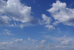 Lots of fluffy white clouds in the blue sky. Clouds large and small. The day is clear, Sunny and windy. Weather is good royalty free stock images