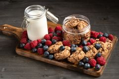 Lots of forest fruits, a jar of milk and cookies, placed over wooden platter stock photos