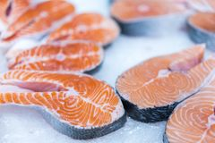 Lots of fresh raw salmon steaks on ice in supermarket. Fresh raw salmon on ice. Big pieces raw salmon. Fish on ice. Salmon on coun. Ter Stock Photo