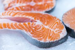 Lots of fresh raw salmon steaks on ice in supermarket. Fresh raw salmon on ice. Big pieces raw salmon. Fish on ice. Salmon on coun. Ter Royalty Free Stock Photography
