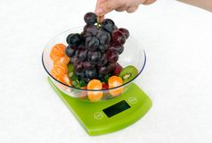 Lots of fruit on the kitchen scale Stock Photography