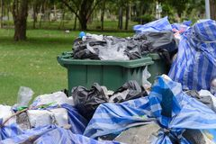 Lots of garbage out of garbage pail on street. In the park stock photo