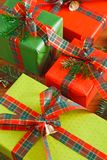 Handmade modern presents in colored paper decorated with red, green satin ribbon bows. Crop, closeup. Lots of gift boxes in stylish modern colored paper Stock Images