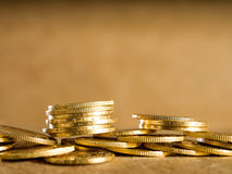 Lots of gold coins. Gold coins over brown background stock photography
