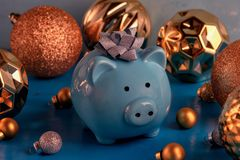 Lots of gold and silver Christmas balls of various sizes. In the center is a small blue piggy bank with a bow on its. Head. Symbol of the new year. Holiday royalty free stock photo