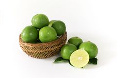 Lots of green lemon are in a wooden basket. And some of the outside with lemon slices cut in half on the side royalty free stock photography