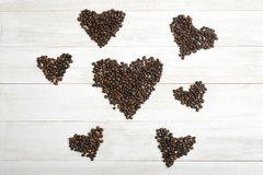 Lots of hearts from coffee beans on wooden surface in top view. Stock Photography