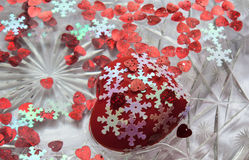 Lots of hearts floating in the water.   Valentine`s day. A red heart. White snowflakes. A dish of water. Heart floats in water Stock Photography