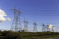 Lots of high voltage power transmission towers with blue sky background Stock Images