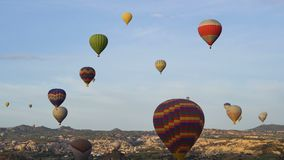 Lots of hot air balloons flying over valleys in Goreme, Turkey. Tourists from all over the world come to Cappadocia to