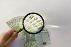 Lots of hundred Euro bills and magnifying glass Royalty Free Stock Image