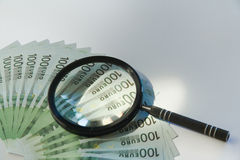 Lots of hundred Euro bills and magnifying glass Royalty Free Stock Photography