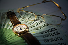 Lots of hundred Euro bills and watch Royalty Free Stock Photo