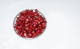 Lots Of Juicy Ripe Pomegranate Seeds On A Glass Bowl With White Background. stock photography
