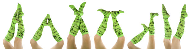 Lots of legs with green music socks Royalty Free Stock Photos