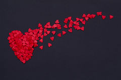 Lots of little red hearts flying on black background. Stock Photo