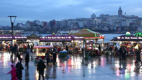 Lots of local people and tourists walking between street vendors near Eminonu Pier. Square in the evening with Golden horn and Galata Tower background in stock video footage