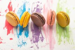 Lots of macarons colored on a color watercolor bright background. Confectionery art concept. Delicious megaltic cookies.  stock photos