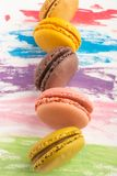 Lots of macarons colored on a color watercolor bright background. Confectionery art concept. Delicious megaltic cookies.  royalty free stock photos