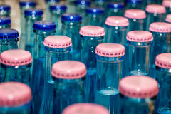 Lots of Mineral water glass bottles. With blue and pink head Stock Photos