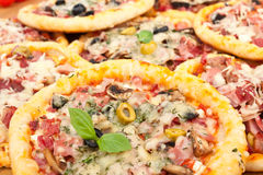 Lots of Mini Pizzas. Lots of Mini Different Pizzas on Top of Each Other Royalty Free Stock Images