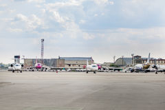 Lots of parked aircrafts in a parking area of a small airport. Maintanenace cars and buildings, cloudy sky on the background Stock Image