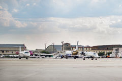 Lots of parked aircrafts in a parking area of a small airport. Maintanenace cars and buildings, cloudy sky on the background Royalty Free Stock Photography