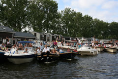 Lots of people in boats during Sail Amsterdam. Lots of people sitting in and on boats in front of Dutch house arks during Sail Amsterdam Royalty Free Stock Photos