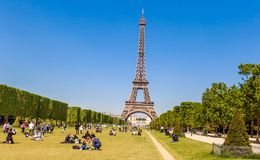 Lots of people relaxing and having fun on Champ de Mars. With the Eiffel Tower on background on a sunny day. Paris, France Stock Photos