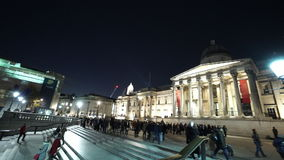 Lots of people at Trafalgar square and National Gallery night shot stock footage