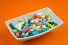 Lots of pills on orange background Royalty Free Stock Photography