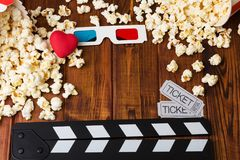 Lots popcorn, 3D-glasses, heart, movie tickets and movie clapper. Lots of popcorn, 3D-glasses, red heart, movie tickets and movie clapper against the dark wood Stock Image