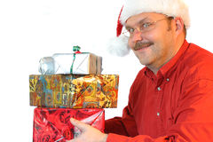 Lots of presents. Man holding some christmas presents in his hands, with a rather crazy look in his eyes stock image