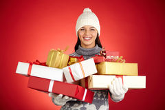 Lots of presents. Cheerful young woman in winterwear holding multi-color giftboxes royalty free stock photography