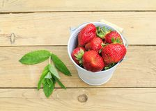 Lots of red ripe strawberries on a wooden table in the garden in Stock Photography