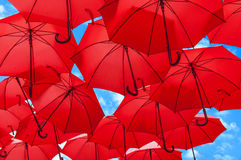 Lots of red umbrellas coloring the sky in the city center agains sky Stock Images