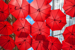 Lots of red umbrellas coloring the sky in the city center Royalty Free Stock Images