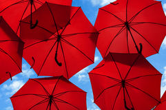 Lots of red umbrellas coloring the sky in the city Stock Photos