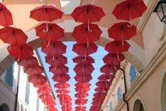 Umbrellas flying in sky over city street  in Venice. Lots of red umbrellas flying in sky over city street  in Venice, Italy Stock Photo
