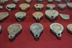 Lots of roman clay oil lamps with zoomorphic motifs. Merida, Spain - December 20th, 2017: Lots of roman clay oil lamps with zoomorphic motifs, National Museum of royalty free stock photo